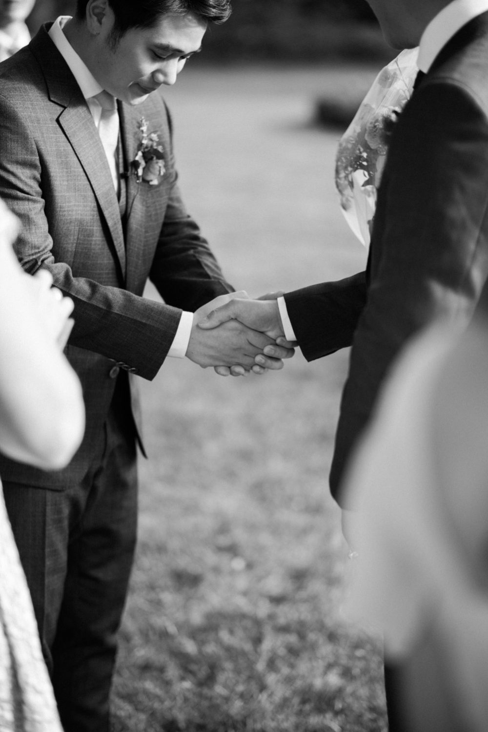 Photo of the groom shaking hands with bride's father during the wedding ceremony