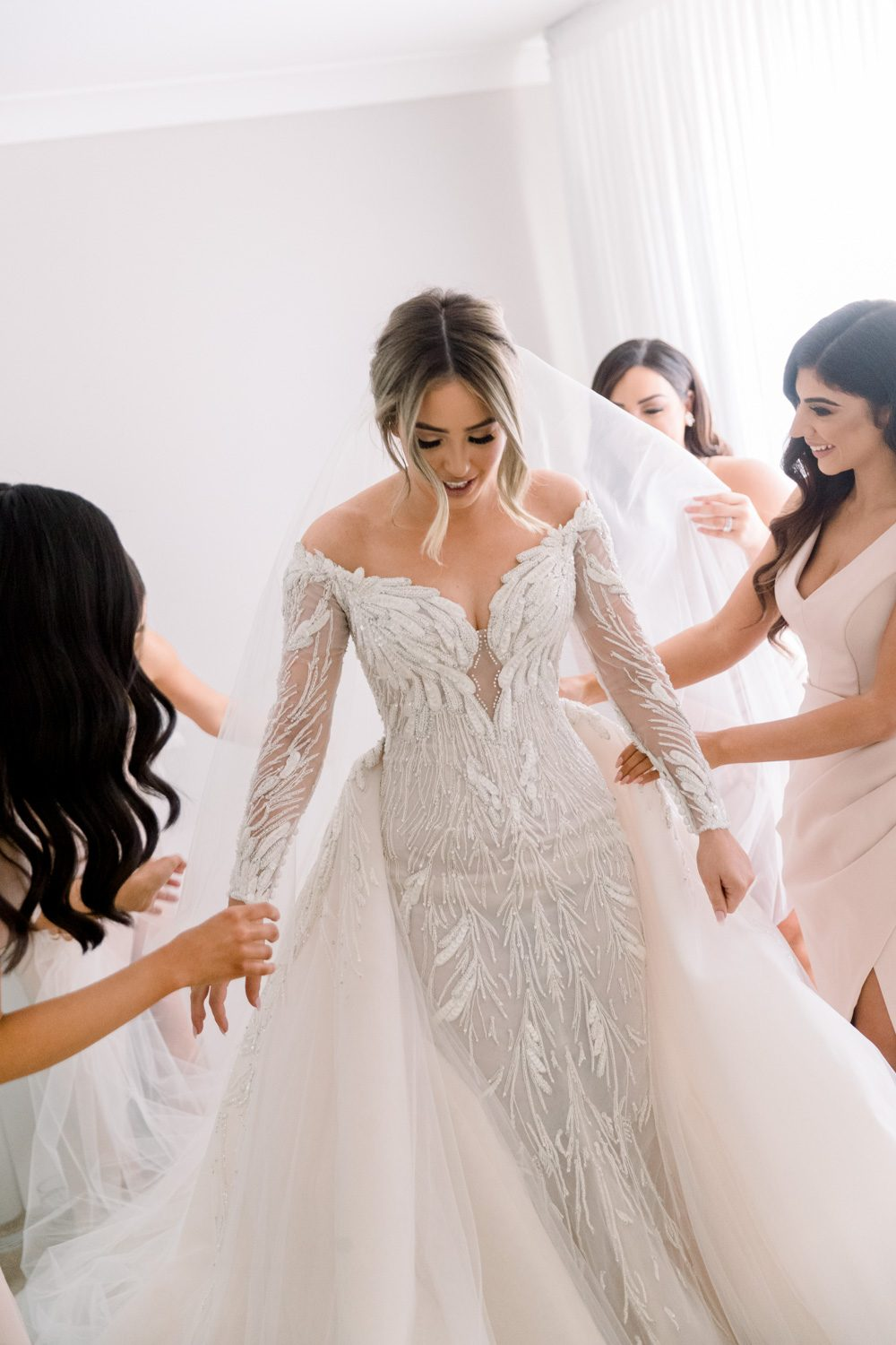 Bride is putting on her steven khalil wedding gown with all the bridesmaids